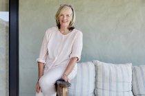 Mulher sentada no braço resto do sofá — Fotografia de Stock