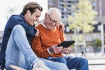 Senior man and grandson using tablet — Stock Photo