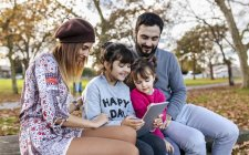Family sitting on bench looking at tablet — Stock Photo