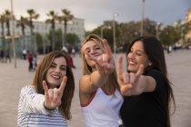 Женщины показаны знак рок-н-ролл — стоковое фото