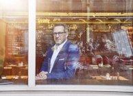 Geschäftsmann aus Fenster im café — Stockfoto