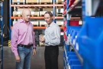 Homens examinando parafuso no armazém — Fotografia de Stock