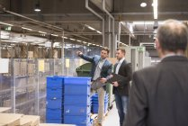 Businessmen standing in factory — Stock Photo