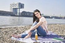 Donna seduta con birra — Foto stock