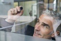 Businessman writing on glass pane — Stock Photo