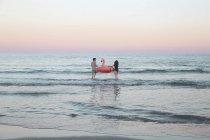 Пара, ходить в море с надувной Фламинго — стоковое фото