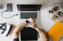 Man using smartwatch at desk — Stock Photo