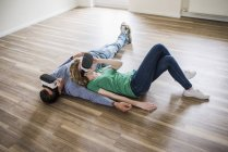 Young couple lying on floor in empty apartment in virtual reality glasses — Stock Photo