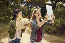 Молодые женщины с планшетом и картой — стоковое фото