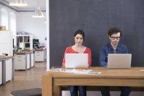 Uomo e donna che utilizza computer portatili — Foto stock