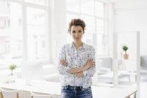 Businesswoman sitting on desk — Stock Photo