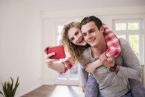 Glückliches junges Paar in neue Heimat nehmen selfie — Stockfoto
