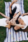 Friends lying on blanket and raising hands — Stock Photo