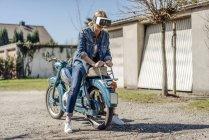Woman sitting backwards on motorcycle — Stock Photo