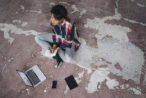 Femme assise sur le sol avec ordinateur portable — Photo de stock