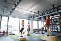 Seniors working out with wooden boxes — Stock Photo