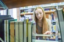 Teenage girl holding book behind bookshelf in library — Stock Photo