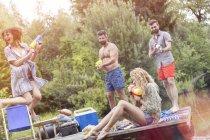 Amis heureux s'amuser avec un pistolet à eau sur une jetée — Photo de stock