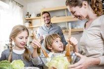 Familie vorbereiten Salat in Küche — Stockfoto