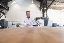 Человек с планом и ноутбук, изучение продукта — стоковое фото