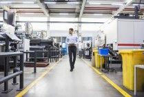 Man with tablet walking in factory — Stock Photo