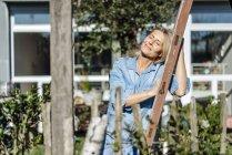 Mujer inclinada de escalera en el jardín - foto de stock
