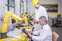 Two engineers in factory looking at device — Stock Photo