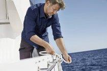 Людина на яхті, пов'язуючи вузол — стокове фото