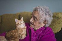 Женщина сидит с тэбби-котом — стоковое фото