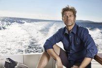Зрелый мужчина, сидящий на моторной яхте — стоковое фото
