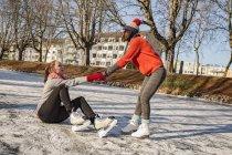 Mulher, ajudando o amigo de patinação no gelo — Fotografia de Stock