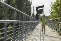 Woman running on bridge — Stock Photo