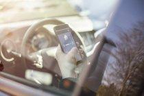 Человек в машине регулирует устройства дома с помощью смартфона — стоковое фото