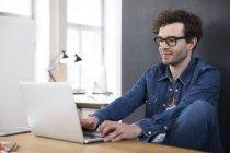 Homme souriant utilisant un ordinateur portable — Photo de stock