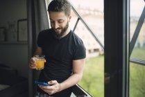 Young man drinking an orange juice — Stock Photo