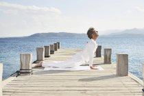 Homem fazendo exercício de ioga no molhe — Fotografia de Stock