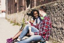 Coppia seduta a terra e mangiare gelato — Foto stock