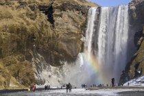 Люди на водопаде Скогафосс — стоковое фото
