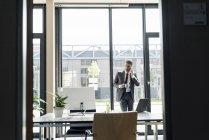 Бізнесмен, стоячи з чашкою кави — стокове фото