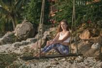 Woman sitting on swing — Stock Photo