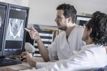 Two doctors discussing x-ray images on computer screen — Stock Photo