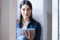 Woman with tablet at the window — Stock Photo