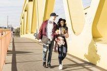 Couple with skateboards walking on bridge — Stock Photo
