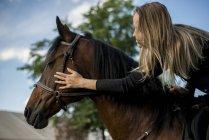 Woman riding stroking horse — Stock Photo