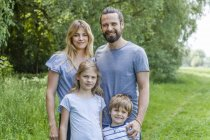 Happy family standing in nature — Stock Photo