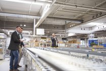 Businessmen standing at conveyor belt — Stock Photo