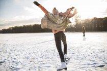 Woman with ice skates on frozen lake — Stock Photo