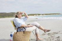 Женщина, сидящая на пляже — стоковое фото