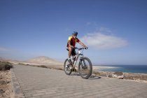 Man on mountain bike riding on pavement — Stock Photo