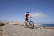 Mann mit Mountainbike fahren auf Asphalt — Stockfoto